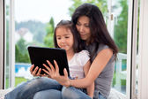 Mother and girl with E-book — Stockfoto