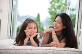 Madre e figlia sul divano ridendo — Foto Stock