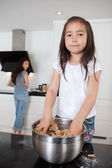 Girl mixing dough with mother in background — Stock Photo