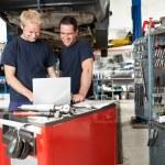 Mechanics with laptop in garage — Stock Photo