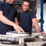 Mechanics Looking at Work Order — Stock Photo