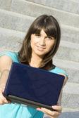年轻女人大街上的一台笔记本电脑. — 图库照片
