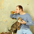 Men with a beer next to the cat steals fish — Stock Photo