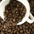Coffee beans are scattered from a white cup - Stock Photo