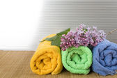 Towels folded lie next to them a branch of lilac — Stock Photo