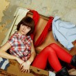 Attractive woman sitting in a suitcase — ストック写真