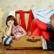 Attractive woman sitting in a suitcase — Стоковая фотография
