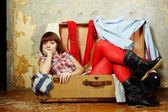 Attraktive frau sitzt in einem koffer — Stockfoto