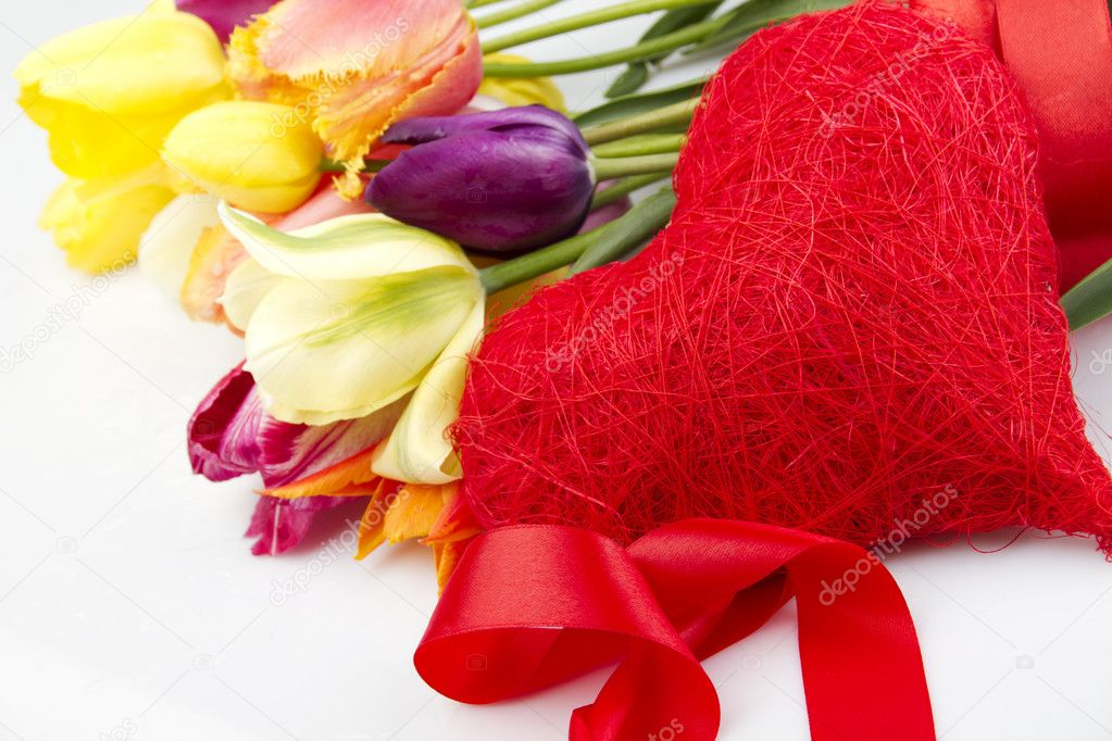 Lovely spring colored tulips with water drops lie in the bouquet in the foreground of the red heart. Isolated — Stock Photo #5852146
