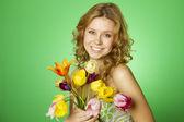 Glückliche junge frau umarmt einen strauß tulpen — Stockfoto