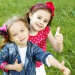 Two little girls friends. Thumbs up - Stock Photo
