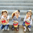 Three little girls friends eat popcorn - Stock Photo