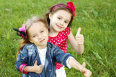 Two little girls friends. Thumbs up — Stock Photo