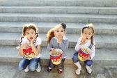 Three little girls friends eat popcorn — Stock Photo