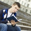 Male student on campus with textbooks — Stock Photo