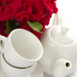 White crockery for tea and a bouquet of roses — Stock Photo