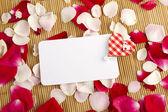 Tarjeta y pétalos de rosa — Foto de Stock
