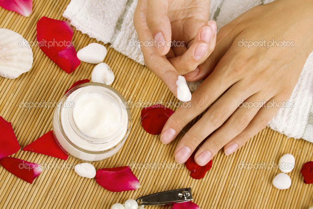 Close-up of girl lying on hand towel next to the cream, rose petals and manicure equipment — Stock Photo #6284969