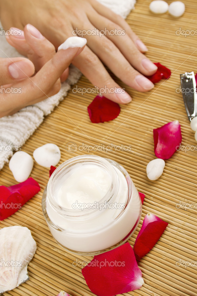 Close-up of girl lying on hand towel next to the cream, rose petals  Stock Photo #6284973