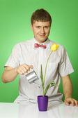Närbild av en ung man vattna en blomma — Stockfoto