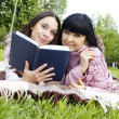Mom and daughter reading a book - Stock Photo