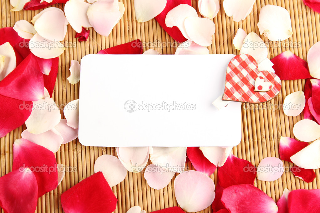 At the rose petals is white piece of paper and a red heart. Postcard  Stock Photo #6379184