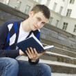 Stock Photo: Male student on campus with textbooks