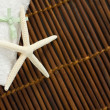 Spa or Wellness Background with White Towel on Bamboo mat - Stock Photo