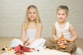Smiling sibling children playing with stuffed animals — Stock Photo