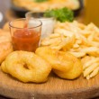 Snack - fried potatoes and squid in restaurant — Stock Photo