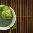 Sea Cosmetic Salt and Green Leaves in white bowl - Spa Backgroun — Stock Photo