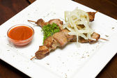 Meat on skewers, onion and red sauce — 图库照片