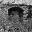 Hooded man next to arched recess of rural ruin — Stock fotografie