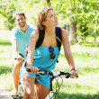 Foto Stock: Young happy couple riding a bicycle