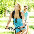Young happy couple riding a bicycle — Stok fotoğraf