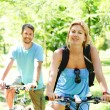 Young happy couple riding a bicycle — 图库照片