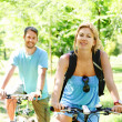 图库照片: Young happy couple riding a bicycle