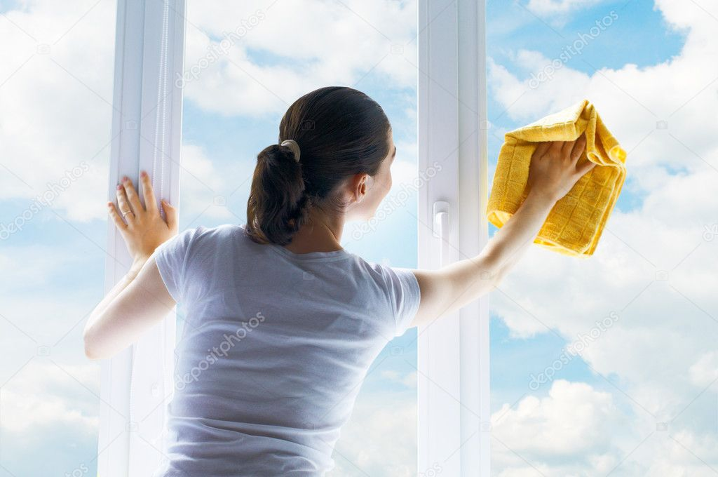 Young woman washing windows — Stok fotoğraf #6638219