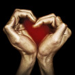 Male hands in gold paint folded in the shape of a heart — Stock Photo