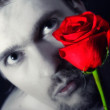 Young man holding a red rose — Stock Photo