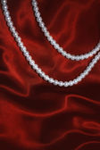 White pearl necklace on a red silk — Stock Photo