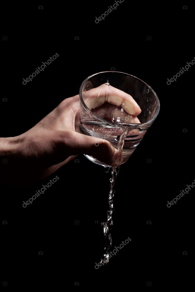 Men's hand poured water from a glass on a black background — Stock Photo #6310422