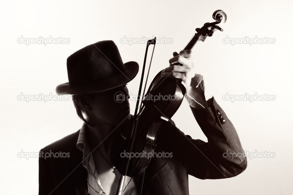 Young violinist playing the violin in hat and jacket  on a light background — Stock Photo #6391210