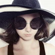 Stock Photo: Young girl in a big round sunglasses and summer hat