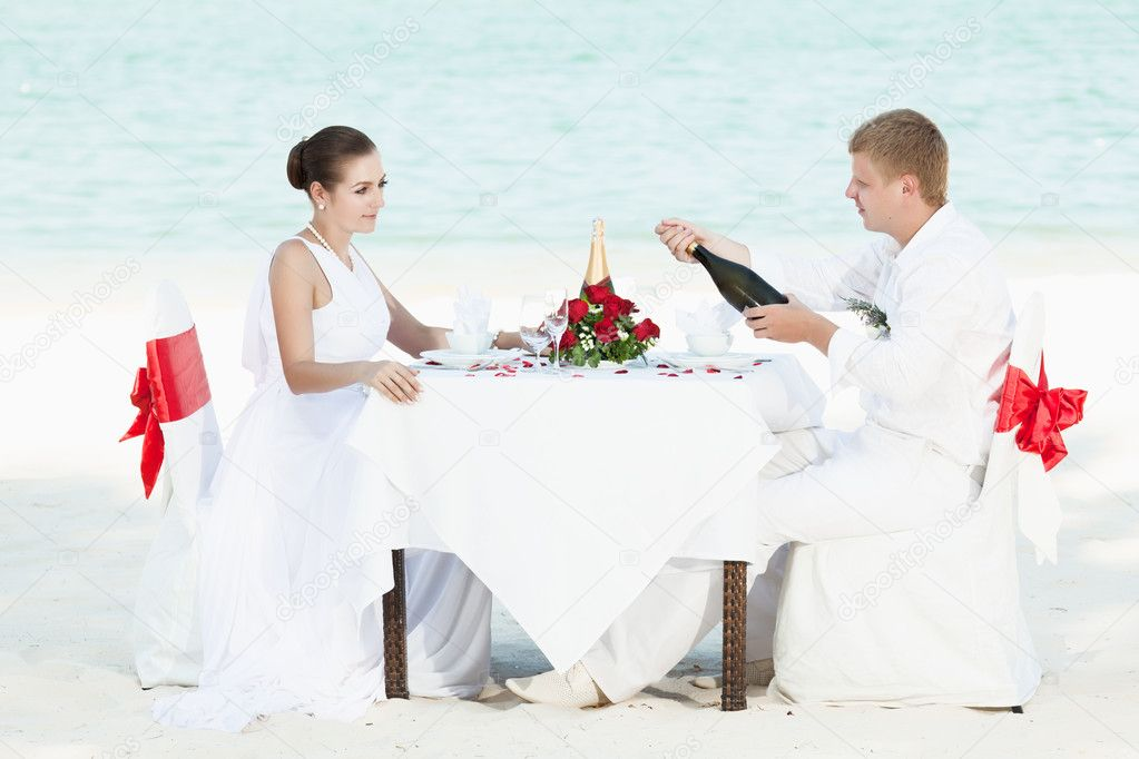 Bride and groom at wedding table on the beach — Stock Photo #5483353