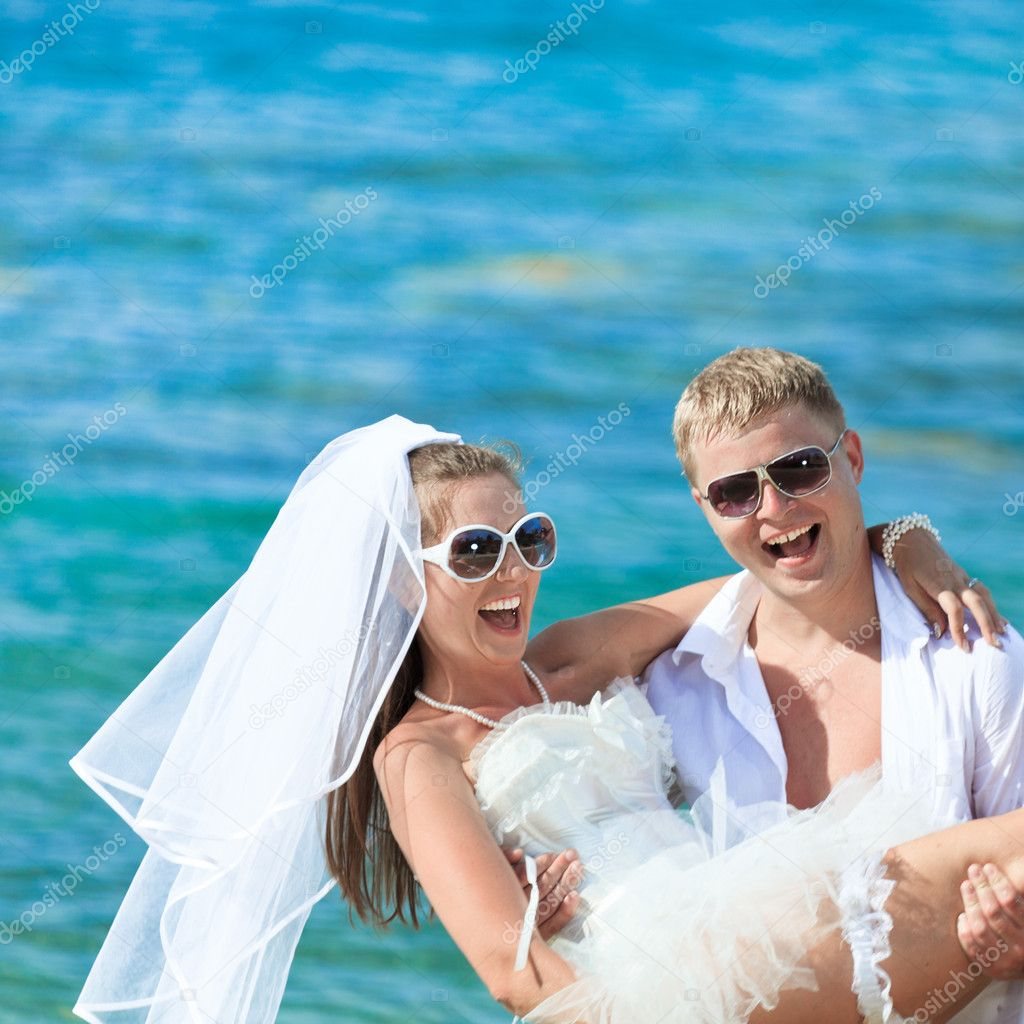 Groom holding up a bride on the beach  Stock Photo #6425390