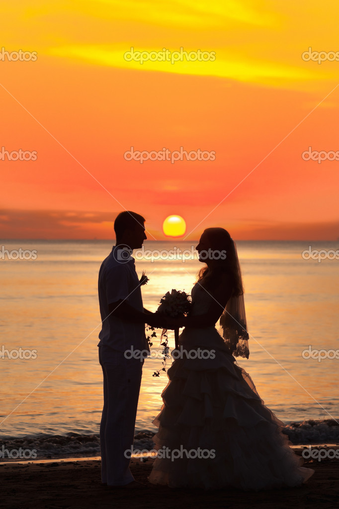 Shape of a bride and groom on the beach at sunrise time — Stock Photo #6600210