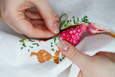 Woman hands doing cross-stitch. A close up of embroidery. — Stock Photo