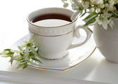Lily of the valley and a cup of coffee — Stock Photo