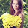 Woman holding yellow flowers . otdoor shoot — Stock Photo